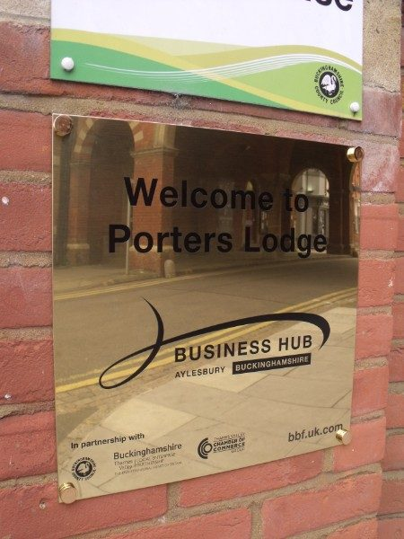 Brass Plaques - plaque engraved with corporate logo and mounted onto brick wall
