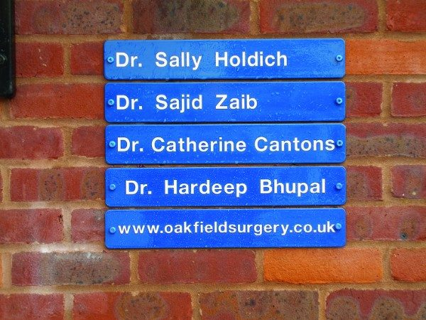 Wall Mounted Anti-Vandal Signs - slat system fitted onto brick wall using colour coded screws
